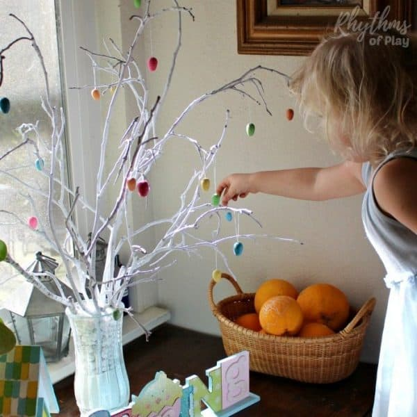 young child decorating a Easter tree with Easter egg tree ornaments