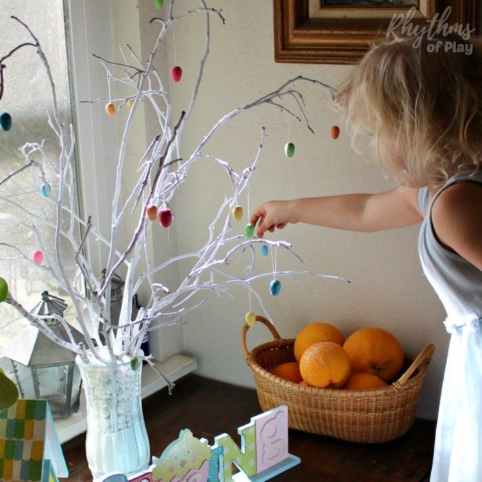 child decorating easter tree with easter ornaments