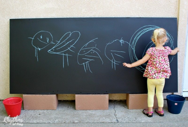 child drawing on a DIY outdoor chalkboard