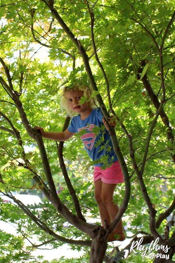 young child climbing a tree smiling