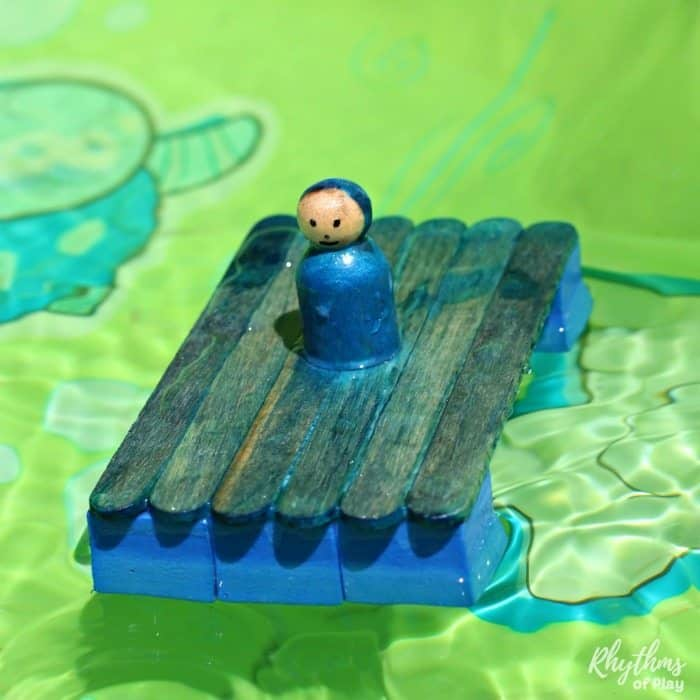 blue craft stick boat with peg doll on top