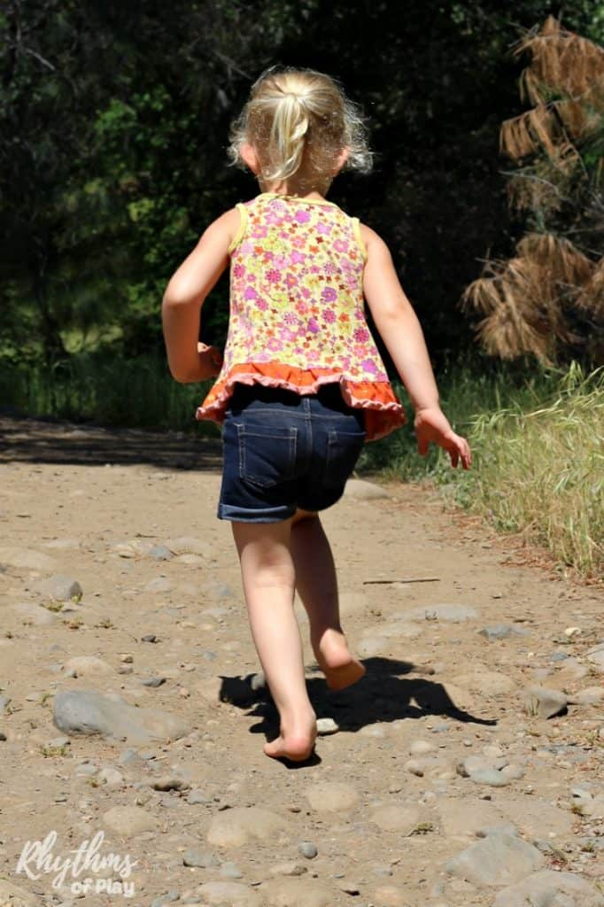 Child running barefoot down a dirt trail.