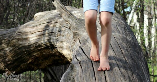 Child walking barefoot outside across a fallen tree barefoot.