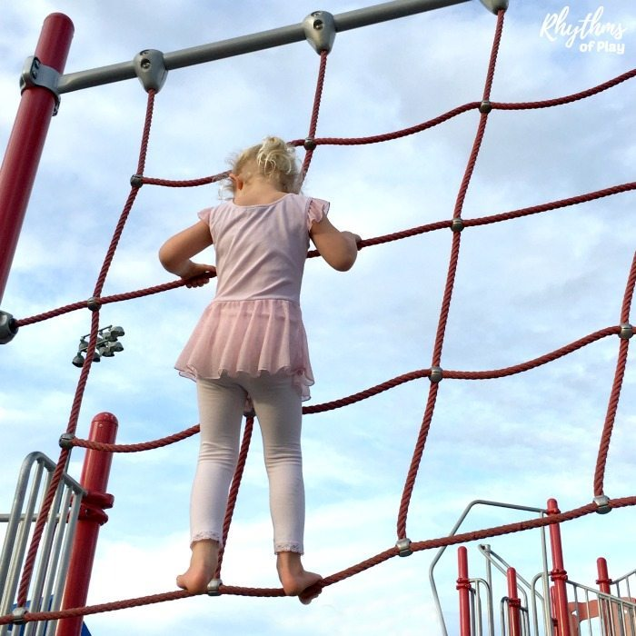 Child playing on rope structure with no shoes on.