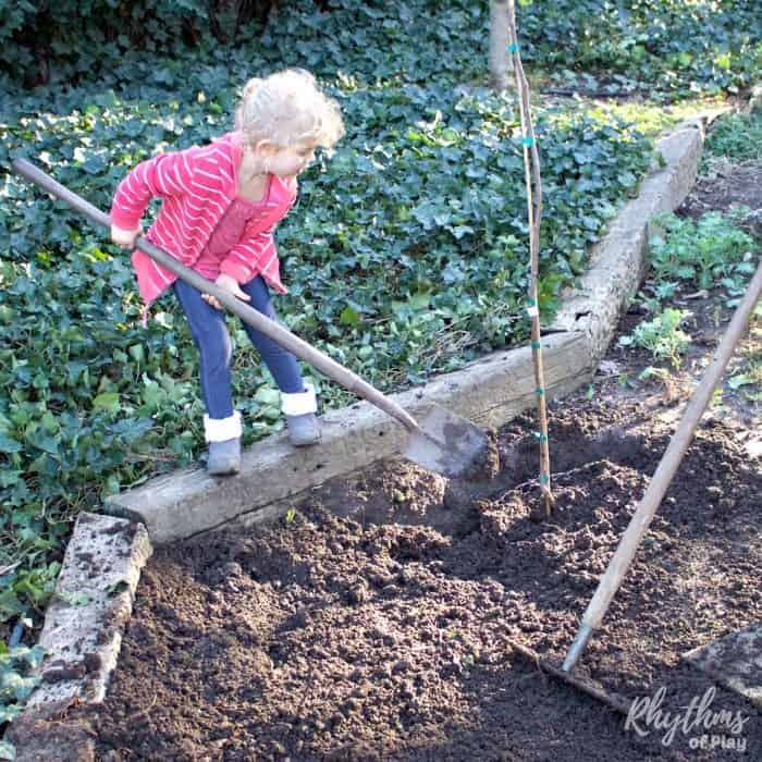 Young child shoveling dirt around a tree