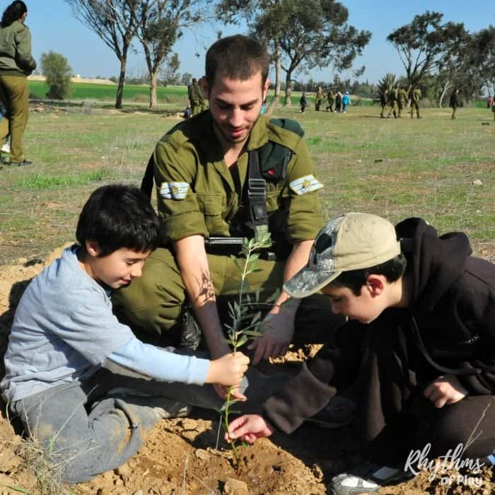 Children planting a tree with the help of a older teen.