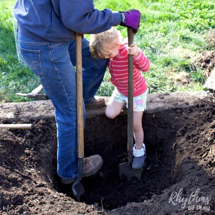 Child and her grandmother digging a hole to plant a tree