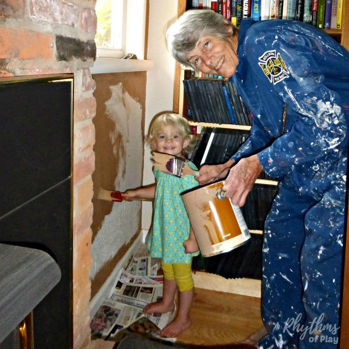 Preschooler helping grandma paint the living room