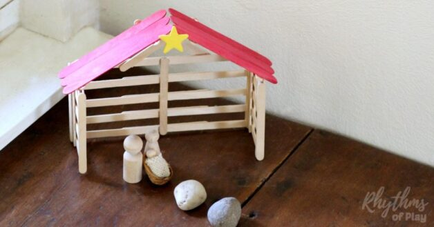 Popsicle Stick Nativity stable Christmas craft pictured with wooden Mary, Joseph, and Jesus