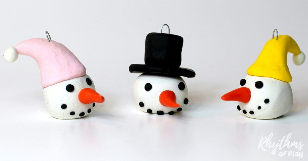 Learning how to make homemade DIY polymer clay Snowman head ornaments is a fun holiday craft for both kids and adults. Handmade ornaments like these easy snowmen with top hats and winter caps are perfect for the Christmas tree. Cute smiling faces like these make beautiful decorations and a great kid-made gift idea!
