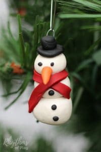 A homemade DIY polymer clay snowman ornament to decorate your Christmas tree! An easy handmade holiday craft and gift idea that kids, teens, and adults can make. They also make a unique hostess gift idea! #ornament #snowman