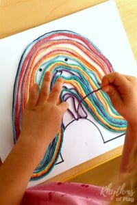 "DIY rainbow yarn art project and fine motor activity for kids preschool age and up. This easy book activity idea was inspired by the children's story ""My Color Is Rainbow."" This fun rainbow craft will help kids learn their colors and strengthen the hand in preparation for writing."