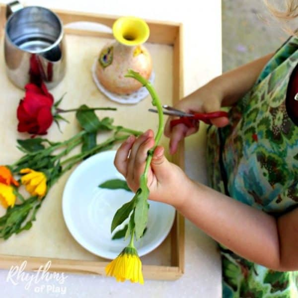 child trimming flowers and arranging flowers