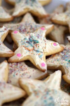 """Cooking with kids is fun! First, use our easy cake mix sugar cookie recipe to make these super soft kindness cookies. Next, make some cream cheese icing. Then decorate with rainbow sprinkles and pass them out as a kindness service project with the kids. My daughter and I were inspired to make these cookies after reading """"The Story of the Kindness Elves."""" Try this kids kitchen book activity and kindness project for kids today!"""