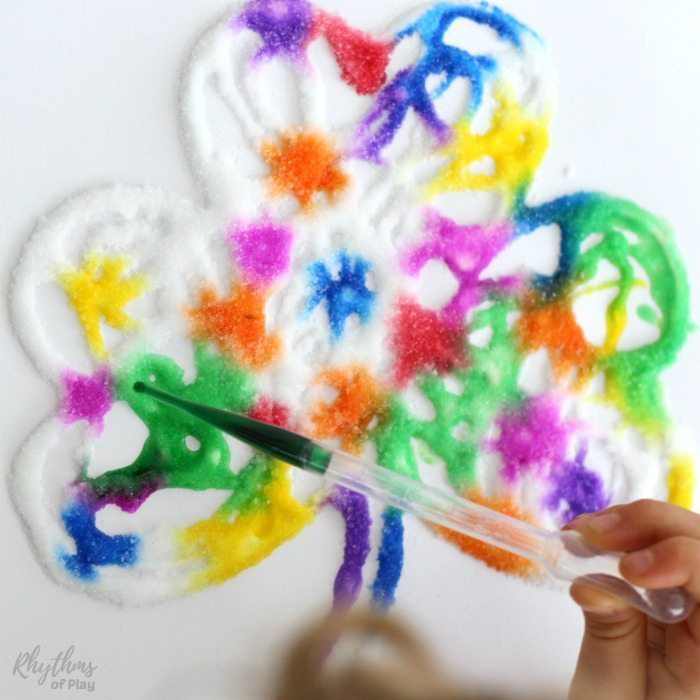 child painting a rainbow shamrock
