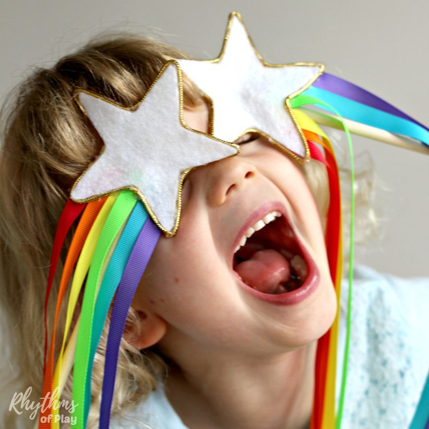 child playing with rainbow ribbon wands