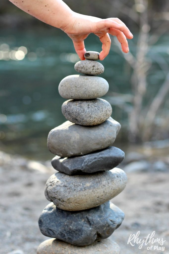 Child balancing a rock on top of a stone stack to create nature land art.