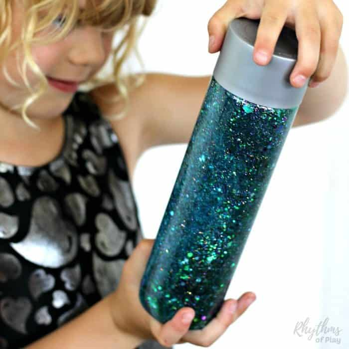 Learn how to make your own glittering mermaid tail sensory bottle! Calm down discovery jars like this glitter sensory bottle can be used for portable no mess safe sensory play, calming an overwhelmed child, and helping children learn to self-regulate. Babies, toddlers, and preschoolers can safely investigate a soothing glittering object without the risk of choking.