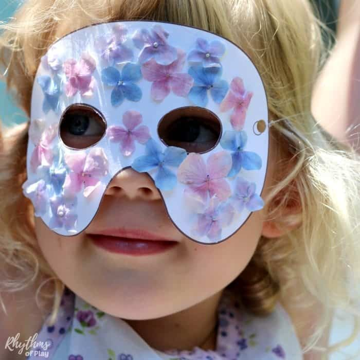 Child wearing nature mask. A nature craft for kids made with real flowers.