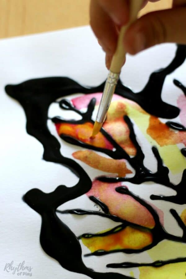 Maple Autumn art with fall leaves art using black watercolor resist medium and primary colors to encourage color mixing.