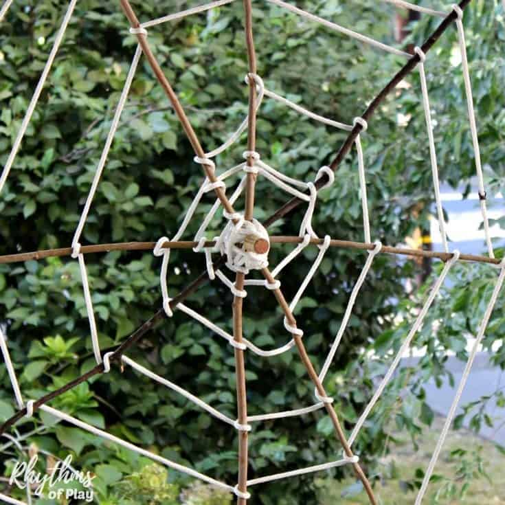 Giant stick spider web Halloween Decoration. An easy nature craft DIY Halloween decoration for your front yard or porch the whole family will enjoy weaving and decorating together!