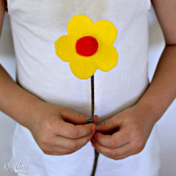 Child holding a single felt flower with a twig stem.