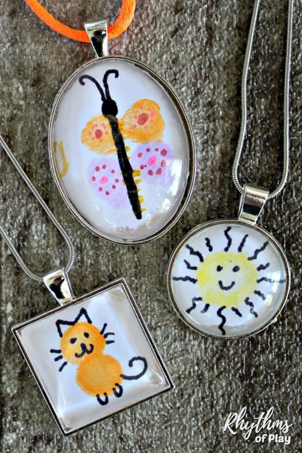 Fingerprint butterfly necklace, fingerprint cat necklace and a fingerprint sun necklace