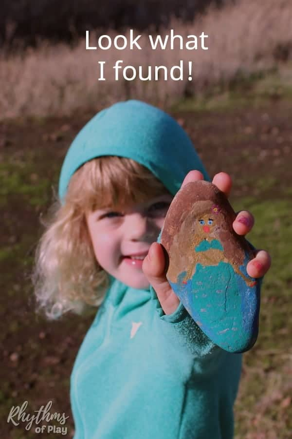 child holding up a found painted mermaid rock