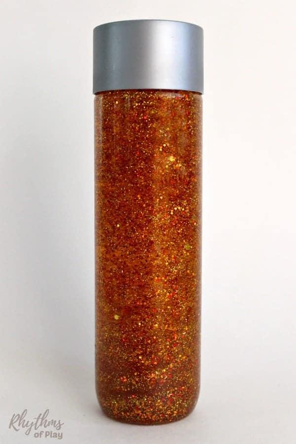 DIY glitter sensory bottle made to look like a sunburst.