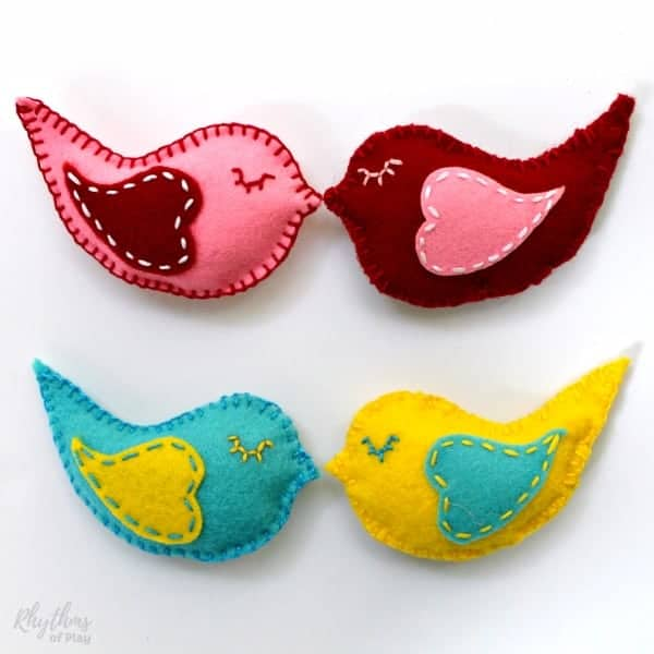 Hand sewn felt lovebirds in pink and red, and blue and yellow.
