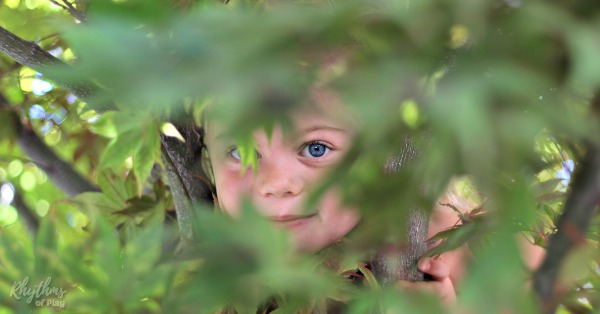 child peeking through foliage in a tree and playing outside