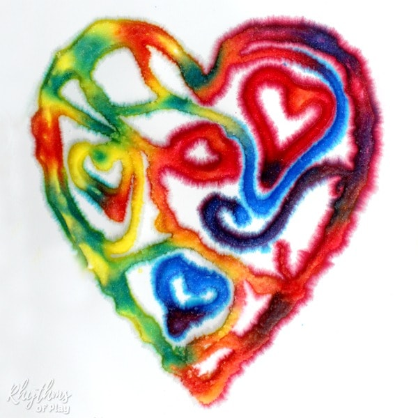 Raised salt paint heart art made with primary colors red, yellow, and blue.