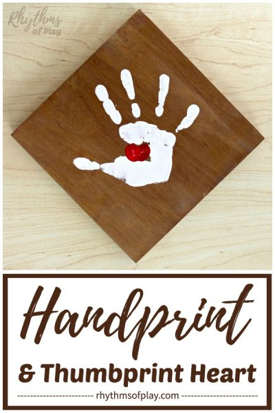 handprint art on wood canvas with a thumbprint heart in the middle