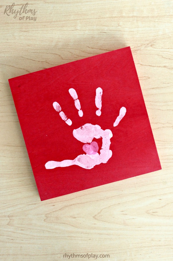 handprint art on wood canvas with thumbprint heart