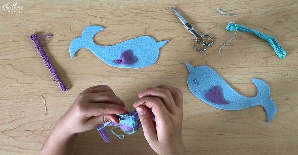 child sewing a narwhal softie