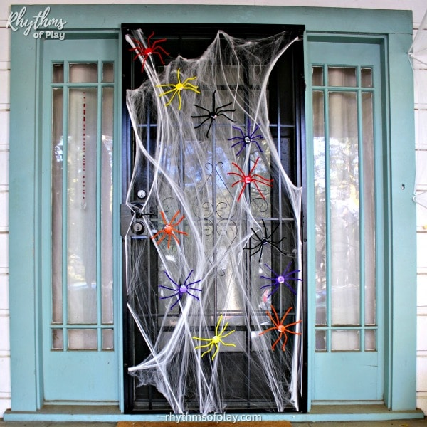 multi-colored Halloween spider decorations running around on a metal security door with stretchy spider web