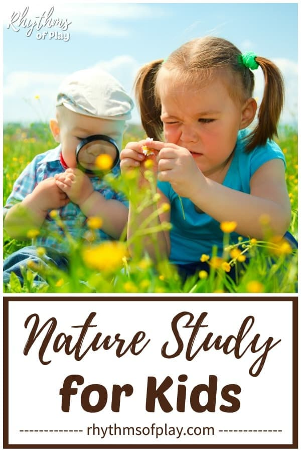 A boy and girl studying nature looking at flowers through a magnifying glass.