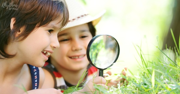 Girl and boy looking through a magnifying glass to study nature.
