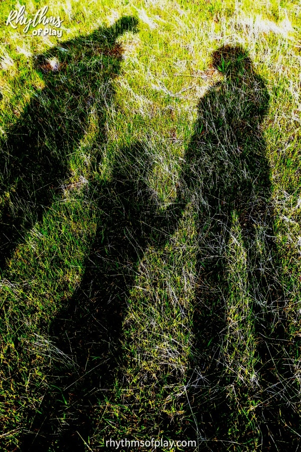 Shadow art photograph with three peoples shadows (mom, dad, and kid) laying in a grassy meadow