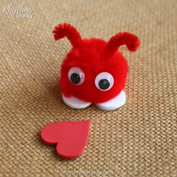 red pom-pom love bug craft looking at a red heart