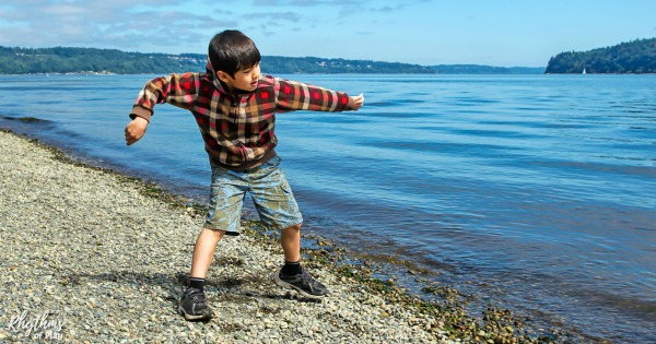Elementary aged kid skipping stones on a rocky shore
