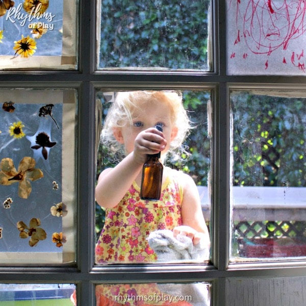Kid washing the windows with glass cleaner from cleaning kit