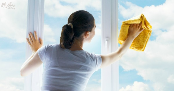 woman washing windows with DIY glass cleaner