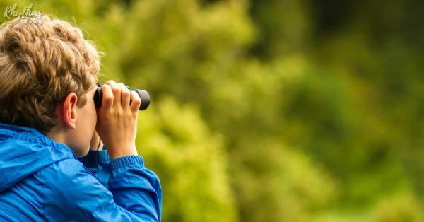 Kid looking through a pair of binoculars bird watching
