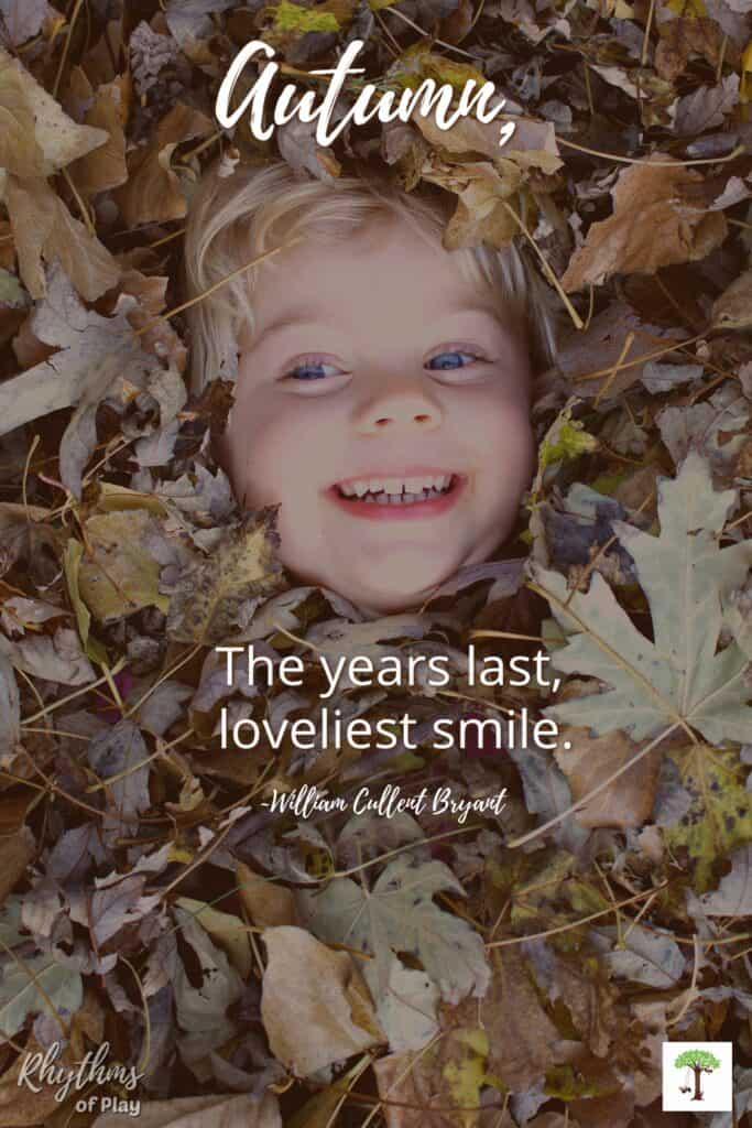 """Childs smiling face showing in a pile of leaves with quote, """"Autumn, the years last, loveliest smile."""""""